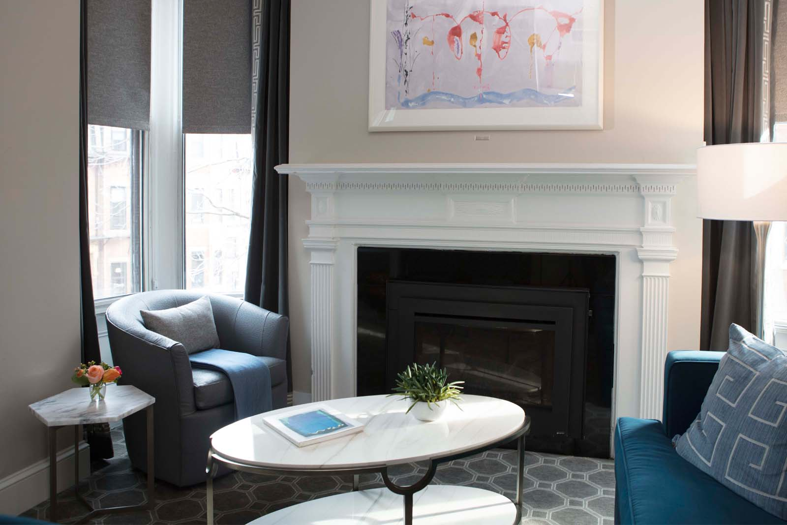 Warm and inviting sitting area with a fire place and artwork in the living room of the queen suite